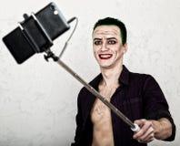 Τύπος με το τρελλό πρόσωπο πλακατζών, την πράσινη τρίχα και το βλακώδες χαμόγελο carnaval κοστούμι παραγωγή της selfy φωτογραφίας Στοκ φωτογραφία με δικαίωμα ελεύθερης χρήσης