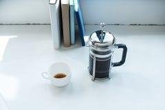 Τύπος με το φλυτζάνι καφέ που στέκεται στο άσπρο γραφείο με τη σειρά των βιβλίων Στοκ φωτογραφίες με δικαίωμα ελεύθερης χρήσης