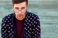 Τύπος μόδας hipster στα γυαλιά μόδας που θέτουν σε ένα ξύλινο μπλε β Στοκ φωτογραφία με δικαίωμα ελεύθερης χρήσης