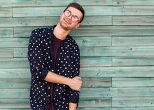 Τύπος μόδας hipster στα γυαλιά μόδας που θέτουν σε ένα ξύλινο μπλε β Στοκ Φωτογραφίες