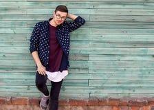 Τύπος μόδας hipster στα γυαλιά μόδας που θέτουν σε ένα ξύλινο μπλε β Στοκ Φωτογραφία