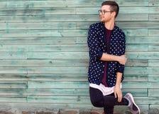 Τύπος μόδας hipster στα γυαλιά μόδας που θέτουν σε ένα ξύλινο μπλε β Στοκ φωτογραφίες με δικαίωμα ελεύθερης χρήσης