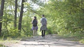 Τύπος πορτρέτου και νέο χαριτωμένο κορίτσι που περπατούν ανά το δασικό ζευγάρι των ταξιδιωτών με τα σακίδια πλάτης υπαίθρια Ζεύγη φιλμ μικρού μήκους