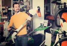 Τύπος που αποφασίζει σχετικά με τον καλύτερο χειρωνακτικό χορτοκόπτη στο κατάστημα εξοπλισμού κήπων Στοκ Φωτογραφία