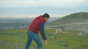 Τύπος που βγάζει το βαρύ σακίδιο, αναπνέοντας το καθαρό αέρα, που απολαμβάνει καταπληκτικός το τοπίο απόθεμα βίντεο