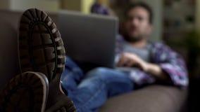 Τύπος που βρίσκεται στον καναπέ στις μπότες και που χρησιμοποιεί το lap-top, κοινωνικοί ιστοχώροι, επικοινωνία στοκ εικόνα