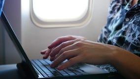 Τύπος που λειτουργεί στο lap-top στο αεροπλάνο κοντά στο παράθυρο απόθεμα βίντεο