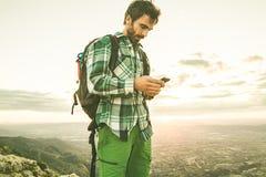 Τύπος που εξετάζει το τηλέφωνο κυττάρων του στο βουνό Οδοιπόρος που εξετάζει το κινητό τηλέφωνό του στα βουνά Στοκ Εικόνες