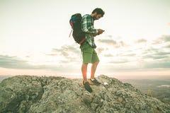 Τύπος που εξετάζει το τηλέφωνο κυττάρων του στο βουνό Οδοιπόρος που εξετάζει το κινητό τηλέφωνό του στα βουνά Στοκ φωτογραφία με δικαίωμα ελεύθερης χρήσης
