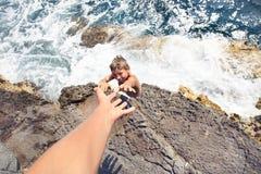 Τύπος που ζητά τη βοήθεια σε κάποιο για να αναρριχηθεί σε έναν απότομο βράχο στοκ εικόνα