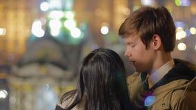 Τύπος που μιλά σε αγαπημένο του και που αγκαλιάζει την, ζευγάρι που απολαμβάνει την καλή θέα βραδιού απόθεμα βίντεο