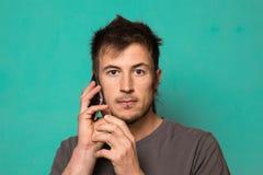 Τύπος που μιλά στο τηλέφωνο κυττάρων του σε ένα μπλε υπόβαθρο Στοκ φωτογραφία με δικαίωμα ελεύθερης χρήσης