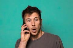 Τύπος που μιλά στο τηλέφωνο κυττάρων του σε ένα μπλε υπόβαθρο Στοκ Εικόνα