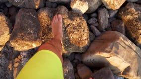 Τύπος που περπατά σε μια δύσκολη ξυπόλυτη έννοια παραλιών των διακοπών ταξιδιού και θάλασσας απόθεμα βίντεο