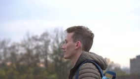 Τύπος που περπατά στη νεφελώδη πόλη Όμορφο νέο καυκάσιο άτομο που φορά το περιστασιακό σακάκι που πηγαίνει κατά μήκος του δρόμου φιλμ μικρού μήκους