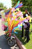 Τύπος που πωλεί τη ζωηρόχρωμα καραμέλα και τα μπαλόνια βαμβακιού σε ένα μηχανικό δίκυκλο στο πορτοκαλί άνθος καρναβάλι Στοκ Φωτογραφίες