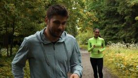Τύπος που τρέχει με τις καθυστερήσεις γυναικών πίσω στο πάρκο φθινοπώρου απόθεμα βίντεο