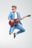 Τύπος που φορά τα γυαλιά ηλίου που πηδούν στο στούντιο παίζοντας την κιθάρα στοκ εικόνες