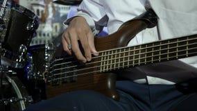 Τύπος στο άσπρο πουκάμισο που παίζει τη βαθιά κιθάρα απόθεμα βίντεο