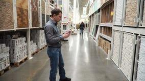 Τύπος στο κατάστημα των δομικών υλικών που επιλέγουν την κάλυψη τοίχων για την ανακαίνιση 4k φιλμ μικρού μήκους