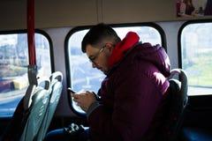 Τύπος στο λεωφορείο που εξετάζει το τηλέφωνο στοκ εικόνες με δικαίωμα ελεύθερης χρήσης