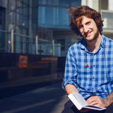 Τύπος στο μπλε πουκάμισο που διαβάζει ένα βιβλίο και ένα χαμόγελο Πορτρέτο του νέου όμορφου μοντέρνου ατόμου στην οδό Στοκ Φωτογραφία
