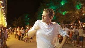 Τύπος, συνεργάτης που χαμογελά στη κάμερα Νύχτα στην οδό οι χοροί, παίζουν τον ανόητο φιλμ μικρού μήκους