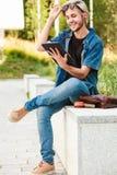 Τύπος χαμόγελου Hipster με τη συνεδρίαση ταμπλετών στην προεξοχή Στοκ φωτογραφία με δικαίωμα ελεύθερης χρήσης