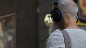 Τύπος Greyhaired στο περιστασιακό άκουσμα τη μουσική κατά τη διάρκεια του περιπάτου απόθεμα βίντεο