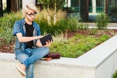 Τύπος Hipster με τη συνεδρίαση ταμπλετών στην προεξοχή Στοκ Εικόνα