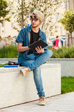 Τύπος Hipster με τη συνεδρίαση ταμπλετών στην προεξοχή Στοκ Φωτογραφίες