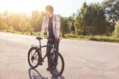 Τύπος Hipster που φορούν το πουκάμισο και τζιν, που στέκονται με το ποδήλατό του, που κοιτάζει κατά μέρος περιμένοντας το φίλο το Στοκ φωτογραφίες με δικαίωμα ελεύθερης χρήσης