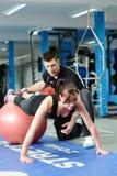 Τύπος UPS στη σφαίρα γυμναστικής με τον προσωπικό εκπαιδευτή στοκ φωτογραφίες