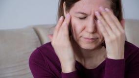 Υγεία και πόνος Τονισμένη εξαντλημένη νέα γυναίκα που έχει τον ισχυρό πονοκέφαλο έντασης φιλμ μικρού μήκους