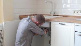 Υγειονομική επισκευή εφαρμοσμένης μηχανικής της διαρροής νερού άτομο που καθορίζει μια στρόφιγγα στην κουζίνα απόθεμα βίντεο