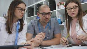 Υγειονομική περίθαλψη, ιατρική: Ομάδα των γιατρών εμπειρογνωμόνων που εξετάζουν τους ιατρικούς διαγωνισμούς σε ένα ιατρικό γραφεί φιλμ μικρού μήκους
