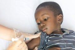 Υγειονομική περίθαλψη και ιατρικό σύμβολο: Το αφρικανικό μαύρο αγόρι παίρνει μια βελόνα εμβολιασμού Στοκ Φωτογραφία