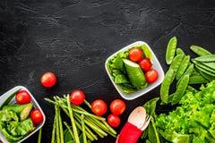 Υγιές γεύμα στα εμπορευματοκιβώτια Σαλάτα με την ντομάτα, αγγούρι στη μαύρη τοπ άποψη υποβάθρου copyspace Στοκ εικόνα με δικαίωμα ελεύθερης χρήσης