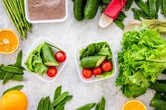 Υγιές γεύμα στα εμπορευματοκιβώτια Σαλάτα με την ντομάτα, αγγούρι, πορτοκάλι στα εμπορευματοκιβώτια στην γκρίζα τοπ άποψη υποβάθρ Στοκ φωτογραφία με δικαίωμα ελεύθερης χρήσης