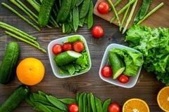 Υγιές γεύμα στα εμπορευματοκιβώτια Σαλάτα με την ντομάτα, αγγούρι, πορτοκάλι στα εμπορευματοκιβώτια στην ξύλινη τοπ άποψη υποβάθρ Στοκ Φωτογραφίες
