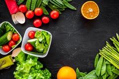 Υγιές γεύμα στα εμπορευματοκιβώτια Σαλάτα με την ντομάτα, αγγούρι, πορτοκάλι στη μαύρη τοπ άποψη υποβάθρου copyspace Στοκ Φωτογραφία