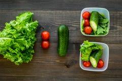 Υγιές γεύμα στα εμπορευματοκιβώτια Σαλάτα με την ντομάτα και αγγούρι στα εμπορευματοκιβώτια στην ξύλινη τοπ άποψη υποβάθρου Στοκ Εικόνες