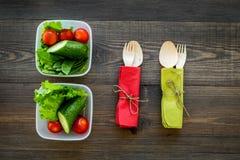 Υγιές γεύμα στα εμπορευματοκιβώτια Σαλάτα με την ντομάτα και αγγούρι στα εμπορευματοκιβώτια στην ξύλινη τοπ άποψη υποβάθρου Στοκ εικόνες με δικαίωμα ελεύθερης χρήσης