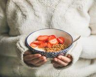 Υγιές γιαούρτι προγευμάτων, granola, κύπελλο φραουλών στα χέρια της γυναίκας Στοκ Εικόνα