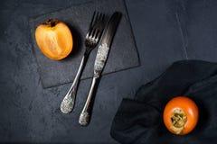 Υγιές επιδόρπιο - persimmon σε ένα μαύρο υπόβαθρο στοκ εικόνες