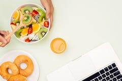 Υγιές επιχειρησιακό μεσημεριανό γεύμα στην αρχή, κύπελλο σαλάτας φρούτων κοντά στο lap-top ο Στοκ Εικόνα