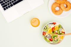 Υγιές επιχειρησιακό μεσημεριανό γεύμα στην αρχή, κύπελλο σαλάτας φρούτων κοντά στο lap-top ο Στοκ φωτογραφίες με δικαίωμα ελεύθερης χρήσης