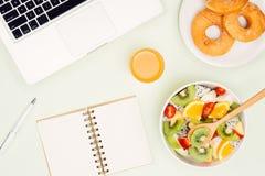 Υγιές επιχειρησιακό μεσημεριανό γεύμα στην αρχή, κύπελλο σαλάτας φρούτων κοντά στο lap-top ο Στοκ εικόνα με δικαίωμα ελεύθερης χρήσης