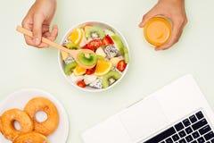 Υγιές επιχειρησιακό μεσημεριανό γεύμα στην αρχή, κύπελλο σαλάτας φρούτων κοντά στο lap-top ο Στοκ φωτογραφία με δικαίωμα ελεύθερης χρήσης