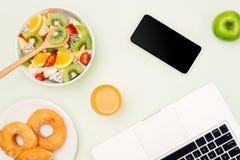 Υγιές επιχειρησιακό μεσημεριανό γεύμα στην αρχή, κύπελλο σαλάτας φρούτων κοντά στο lap-top ο Στοκ Φωτογραφία